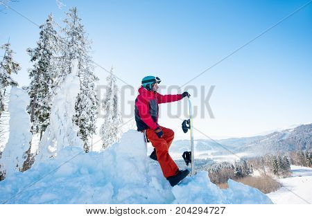Full Length Shot Of A Male Snowboarder Resting On Top Of A Slope Enjoying Stunning Mountains View On
