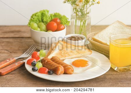 Homemade breakfast with sunny side up fried egg toast sausage fruits vegetable strawberry jam and orange juice in side view with copy space.Delicious homemade american breakfast concept for background. American breakfast on breakfast table.