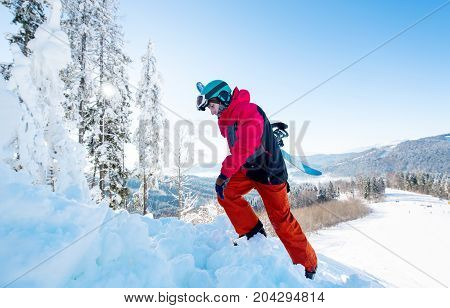 Full Length Shot Of A Freerider Snowboarder Carrying His Snowboard, Climbing Up To The Mountain Copy