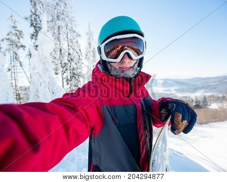 Shot Of A Young Man Snowboarder Taking A Selfie, Wearing Helmet, Skiing Mask And Colorful Winter Sno