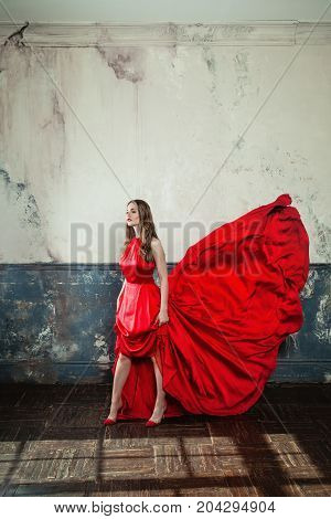 Sexy Model Woman in Red Blowing Dress. Beautiful Fashion Model on Vintage Background