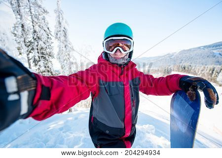 Shot Of A Man Snowboarder Taking A Selfie, Wearing Helmet, Skiing Mask And Colorful Winter Snowboard