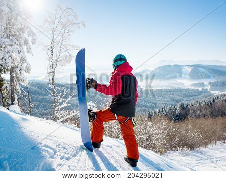 Rear View Of Snowboarder Standing On Top Of A Slope Looking Around Enjoying The View At Winter Ski R