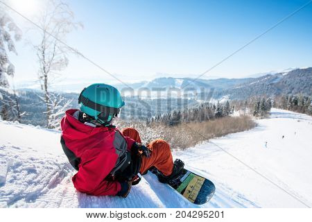 Rearview Shot Of A Relaxed Man Snowboarder Lying On The Snowy Slope Enjoying Stunning Mountains View