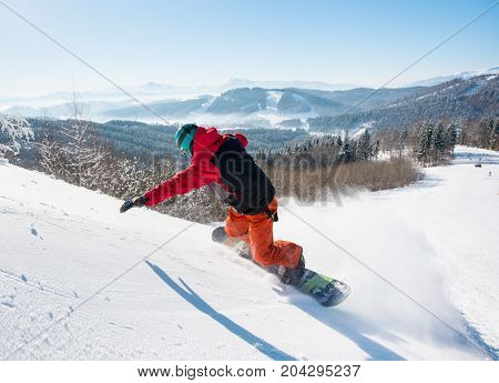 Rearview Shot Of A Freerider Snowboarder Riding Down On The Snowy Slope At Winter Ski Resort In The