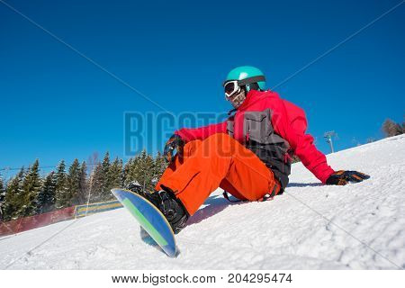 Male Snowboarder Sitting, Relaxing On The Slope Of The Hill At Winter Ski Resort. Blue Sky, Forest O