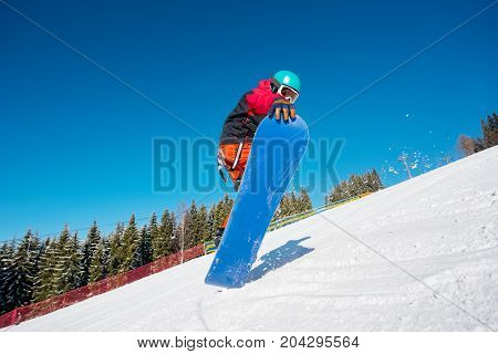 Low Angle Shot Of A Male Snowboarder Jumping While Skiing On The Slope In The Mountains On A Beautif