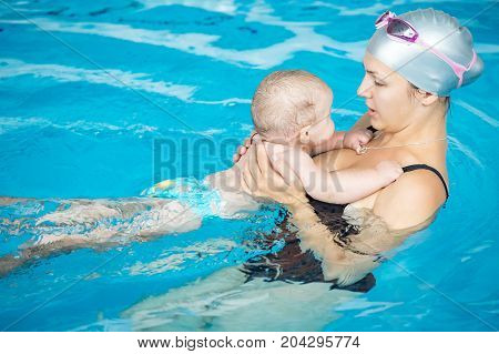 Happy little boy having fun with his mother in a swimming pool