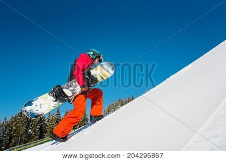 Full Length Shot Of A Fully Equipped Snowboarder Walking Up The Slope At Winter Ski Resort Bukovel,