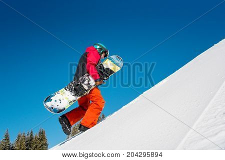 Full Length Shot Of A Fully Equipped Snowboarder Freerider Walking Up The Slope Carrying His Snowboa
