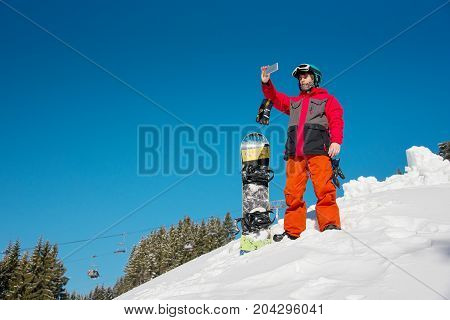 Full Length Shot Of A Male Snowboarder At Ski Resort Using His Smart Phone While Resting After Snowb