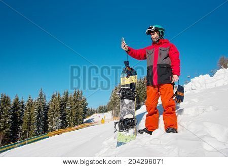 Male Snowboarder Resting On The Slope At Ski Resort, Using His Smart Phone After Snowboarding, Takin