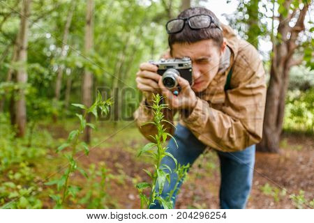 Men biologist in glasses photograph plants in summer forest
