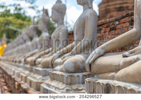 Close focus on hand of meditating monk statue in the row of many statues inside brick temple called Wat Yai Chai Mongkol in Ayutthaya of Thailand