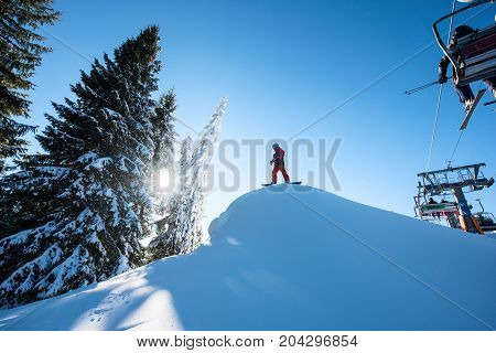 Low Angle Shot Of A Snowboarder Standing On Top Of The Ski Slope Preparing To Ride. Ski-lift On The