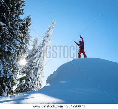 Male Snowboarder Freerider Standing On Top Of The Ski Slope With His Arms In The Air In Victorious G