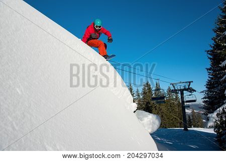 Shot Of A Snowboarder Riding On Dangerous Slope At Winter Ski Resort In The Mountains At Sunny Day.