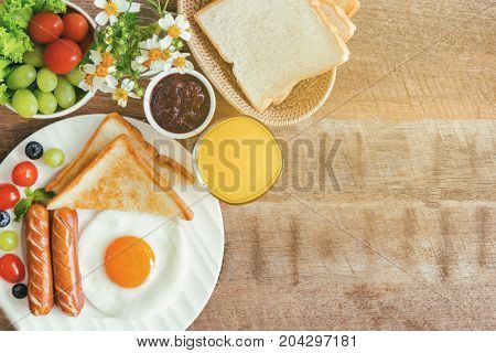 Homemade american breakfast with sunny side up fried egg toast sausage fruits vegetable strawberry jam and orange juice in top view flat lay. Delicious american breakfast on wood table. American breakfast on breakfast table with copy space.