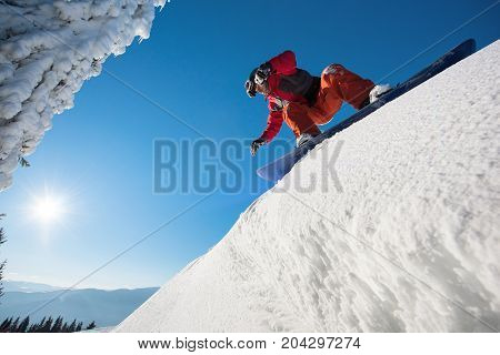 Low Angle Shot Of A Snowboarder Preparing To Riding Downhill In The Mountains On A Beautiful Sunny W