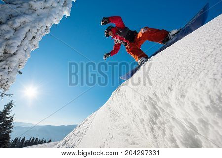Low Angle Shot Of A Snowboarder Riding Downhill In The Mountains Blue Skies On The Background Recrea