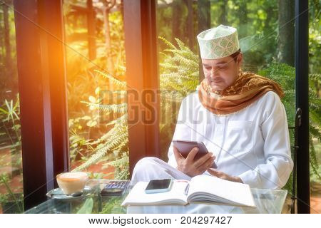 Arab muslim business man sit in coffee shopuse tablet and smart phonebook on glass tablefreelance lifestyle no working space concept.