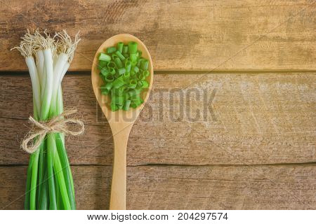 Fresh spring onion tie with rope on wood table. Close up chopped scallions or spring onion in top view flat lay.Prepare spring onion for cooking. Food and vegetable concept for background or wallpaper. Chopped scallions prepare for cooking.