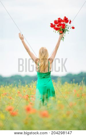 Blonde slim woman in green dress on a red poppy meadow with bouquet of beautiful flowers in one hand.