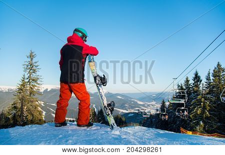 Rear View Shot Of A Snowboarder Standing With His Snowboard, Observing Nature At Ski Resort On A Bea