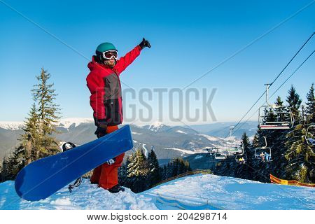 Full Length Shot Of A Snowboarder Standing On The Top Of The Mountains, Showing Thumb Up, Enjoying B