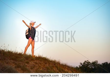 Successful girl backpacker standing on the hill with open arms and enjoys the sunset