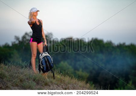Successful girl backpacker standing on top of the hill with backpack in her arm and enjoys the sunrise. Misty forest background