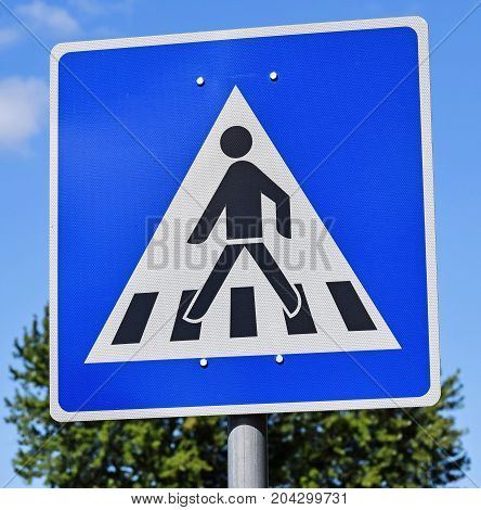 Pedestrian crossing sign on the road in the city