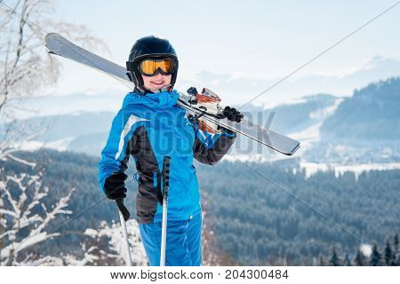 Portrait Of Happy Female Skier Smiling To The Camera, Wearing Skiing Equipment, Holding Skis On The