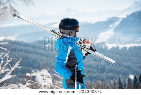 Close-up Female Skier With Her Skis On The Shoulder, Enjoying Beautiful Sunny Day At Winter Ski Reso