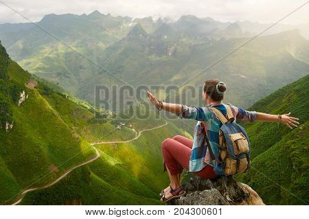 Happy and joyful hiker with raised hands enjoying view at mountains in North Vietnam. Travel to Asia happiness emotion summer holiday concept.