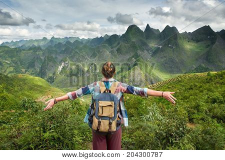 Hiker in mountains enjoying on view of beatiful karst mountains North Vietnam. Mountains and landscape travel to Asia happiness emotion summer holiday concept