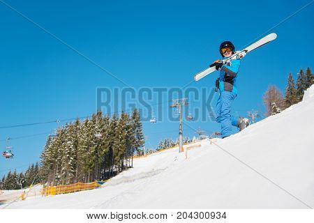 Shot Of A Female Skier Walking Down The Hill In Snowy Mountains At Ski Resort, Carrying Her Skis Cop