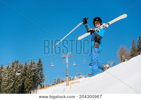 Low Angle Shot Of A Cheerful Woman Standing With Her Skis On The Shoulder On Snowy Slope At Winter S