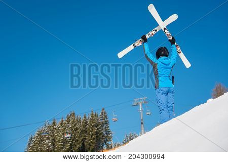 Rear View Of A Female Skier Posing On The Slope Of The Mountain On A Sunny Winter Day, Holding Her S
