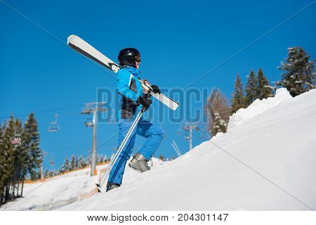 Woman Skier Walking Up The Slope In The Mountains Carrying Her Skis On The Shoulder Copyspace