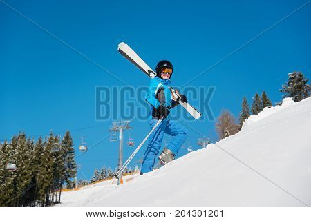 Low Angle Full Length Shot Of A Cheerful Female Skier Carrying Her Skis Smiling To The Camera While