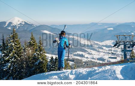 Smiling Woman Skier Standing On Top Of A Mountain, Holding Skis On The Shoulder. Copyspace Winter Sn