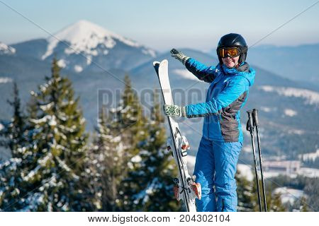 Shot Of A Smiling Woman Skier Standing On Top Of A Mountain At Ski Resort, Pointing At Stunning Natu