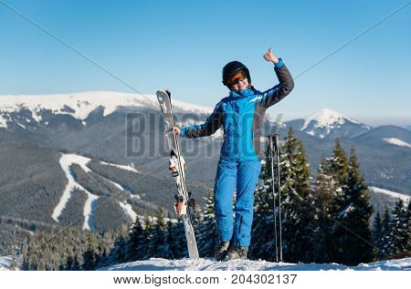 Full Length Shot Of A Cheerful Woman Skier Showing Thumbs Up On Top Of A Mountain With Her Skis At S
