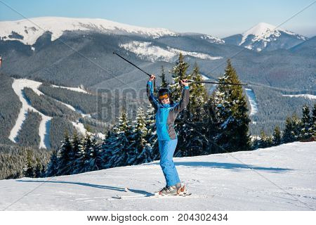 Full Length Shot Of A Happy Female Skier Standing On Top Of The Mountains At Ski Resort, Celebrating