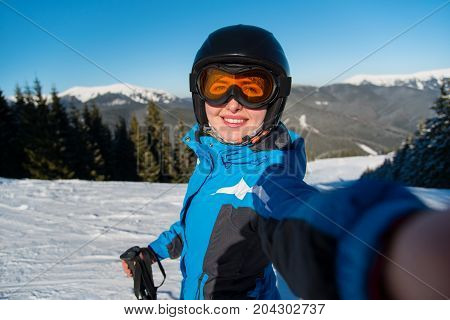 Close-up Portrait Of Cheerful Female Skier Smiling Joyfully Taking A Selfie While Resting On The Slo