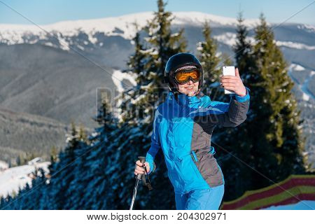 Close Up Shot Of A Woman Skier Smiling Taking A Selfie With Her Smart Phone While Skiing In The Moun