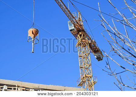 Tower crane at the construction site against sky