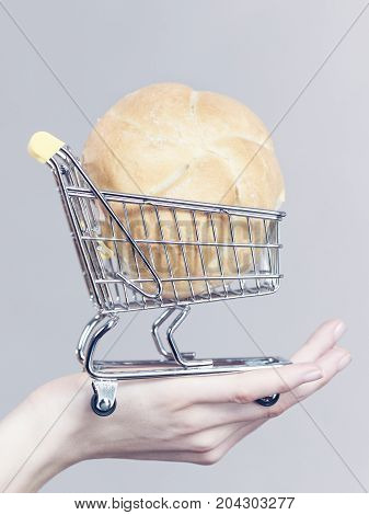 Hand Holding Shopping Cart With Bread