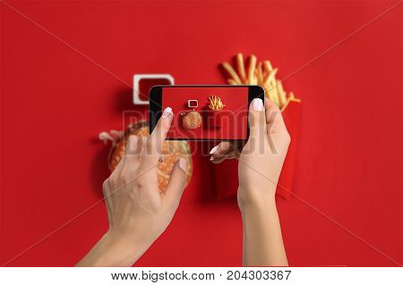 A young woman taking photo of food on smartphone, photographing meal with mobile camera. Made for social networks. Top view mobile phone
